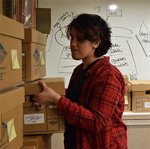 Pooja Desai moves a box on to a bookshelf
