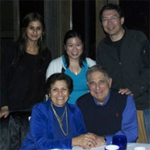 Members of the A/P/A Institute stand behind Jack and Bernice Shaheen who sit at a table, holding hands