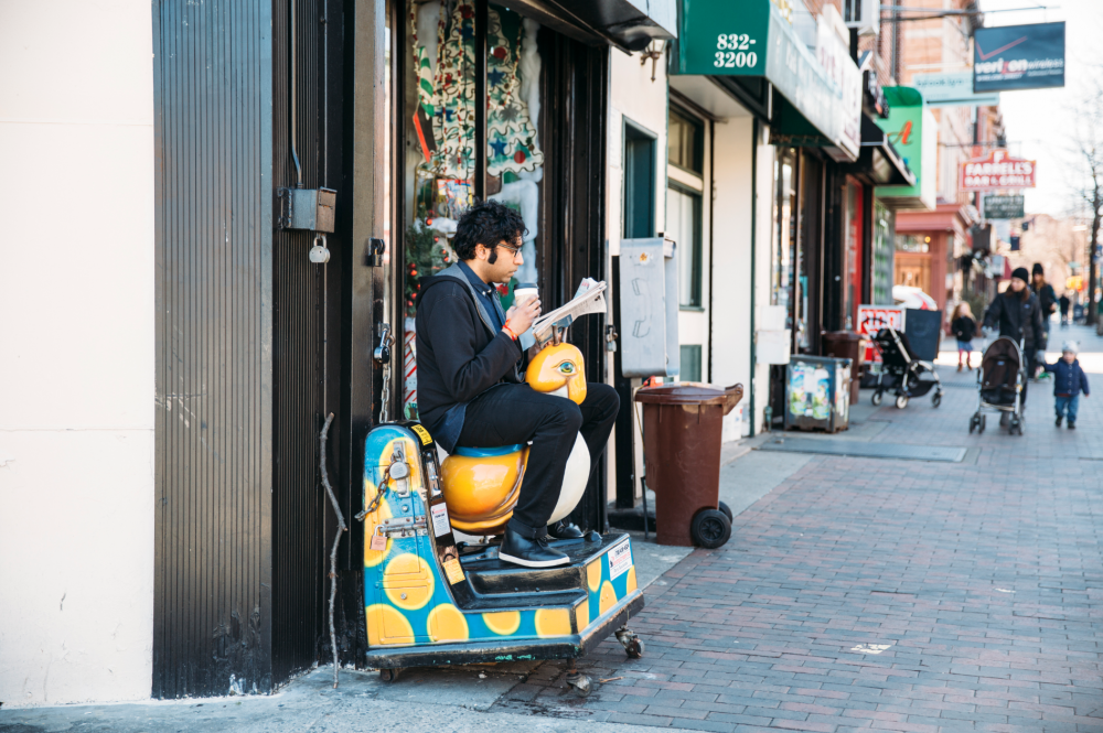 Hari Kondabolu sitting on a mechanical children's ride