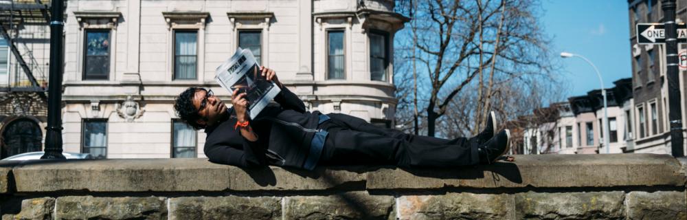 Hari Kondabolu laying down on a wall, reading a newspaper