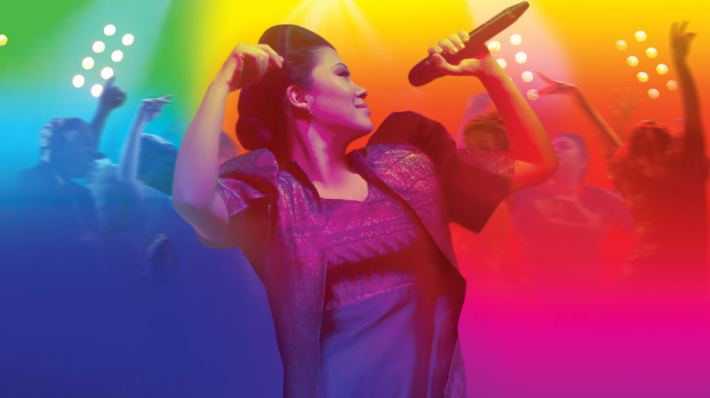 Poster for Here Lies Love. A woman is smiling, arms thrown up, microphone in hand. Behind her, people are dancing underneath rainbow lights.