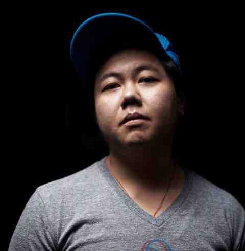 Photo of Kit Yang. He is wearing a grey t-shirt and a blue baseball cap. He has a somber expression.
