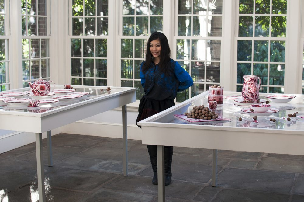 Artist standing between two tables featuring sculptural installations of red and white tea and dining sets
