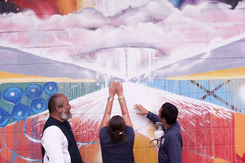 Three individuals discussing mural while standing in front of it