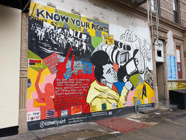 Colorful mural of young girl speaking into a bullhorn with information on rights