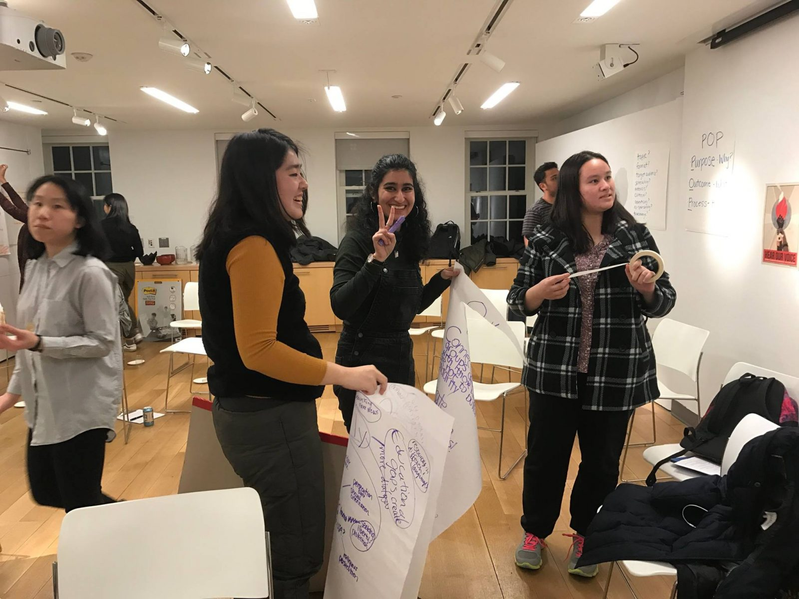 Students at a collaborative workshop brainstorming on large pieces of paper