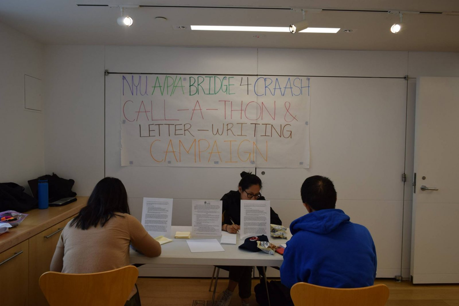 Photograph of three students working on a call-a-thon and letter-writing campaign