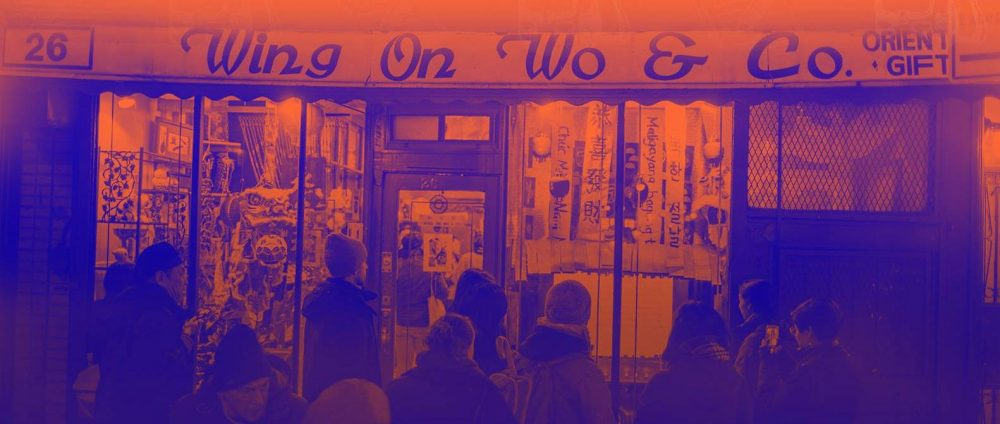 "Blue and orange tinted photograph of storefront, ""Wing On Wo & Co"" with New Year's decorations"