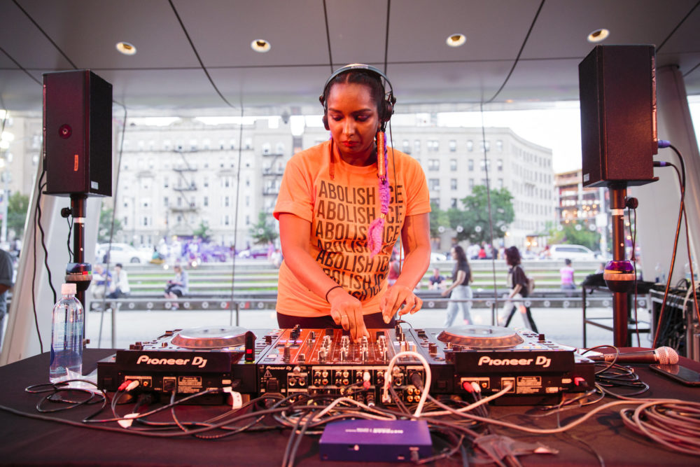 "Uskha DJs at Target First Saturdays at the Brooklyn Museum in July 2018. She wears an orange t-shirt that reads ""Abolish Ice."""