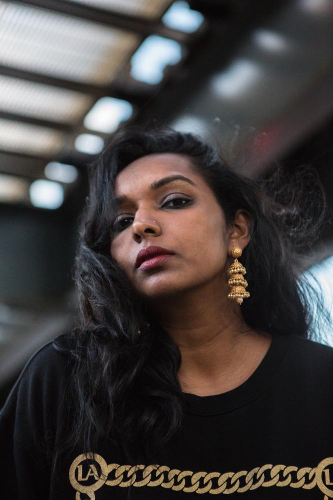 Thanushka Yakupitiyage / Ushka looks down at the camera. She is wearing a black tshirt and gold earrings.