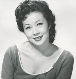 A black and white photograph of Michi Kobi from the chest up. She is looking at the camera and smiling.