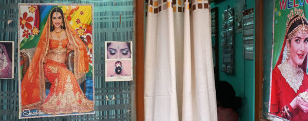Photo of a room with curtain and Bollywood images on walls.