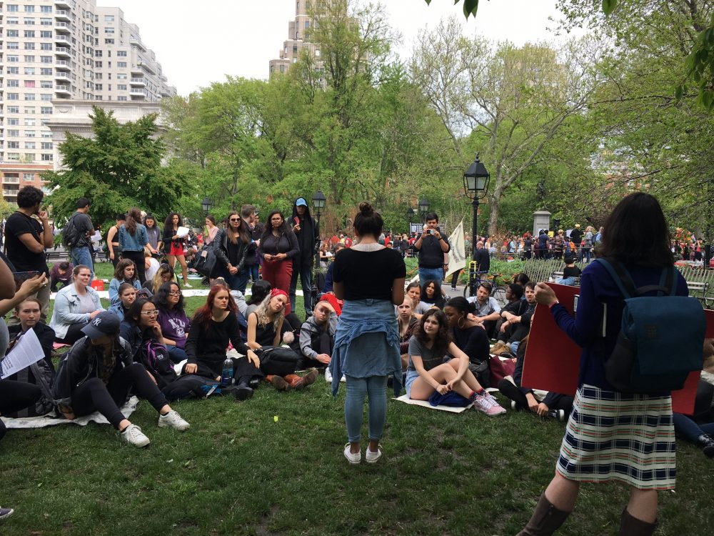 Student members of NYU Sanctuary sit gathered in Washington Square Park during a demonstration.