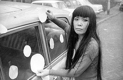 Black and white photograph of artist Yayoi Kusama, sticking paper dots on an automobile.