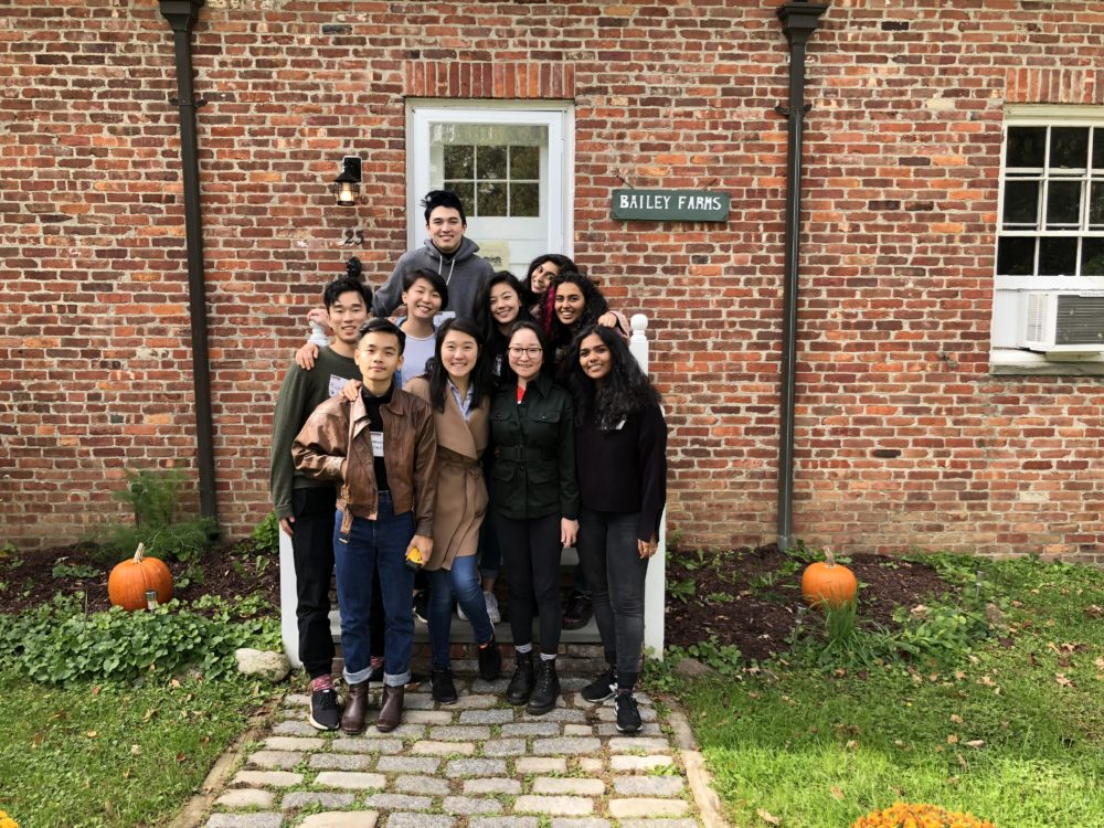 2018-19 A/P/A BRIDGE members stand in rows in front of a brick building. They are facing the camera and smiling.