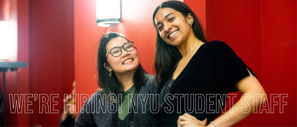 """Two A/P/A student staffers stand smiling towards the camera from the waist up. The text across the image reads """"We're Hiring! NYU Student Staff"""""""