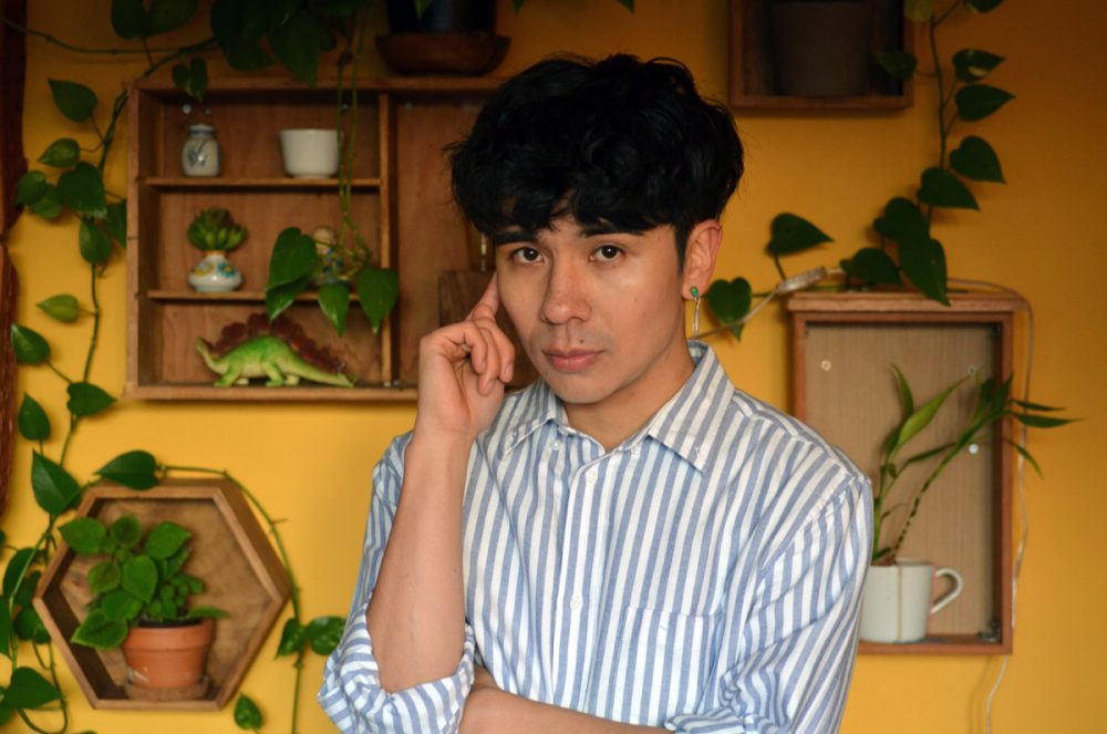 Photograph of Ocean Vuong, who is pictured from the waist up, looking into the camera. He stands in front of a yellow wall that is decorated with plants and small objects.