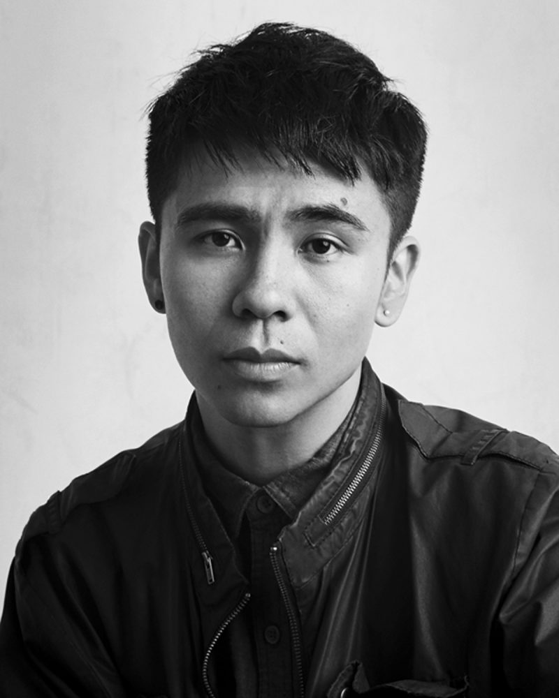 Black and white photo of Ocean Vuong. He is pictured from the chest up and looks at the camera.