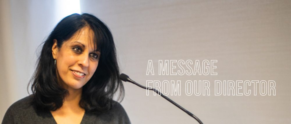 "Crystal Parikh smiling and photographed frm the shoulders up. She looks to the right of the camera. There is a microphone in front of her. Text over the phoograph reads, ""A Message From Our Director."""