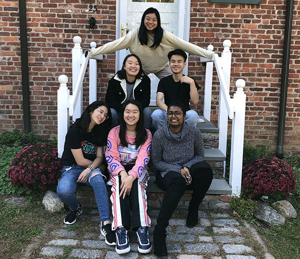 The 2019-20 A/P/A BRIDGE Cohort poses at Bailey Farms, the site of their Fall retreat. They sit and stand on steps, outdoors.