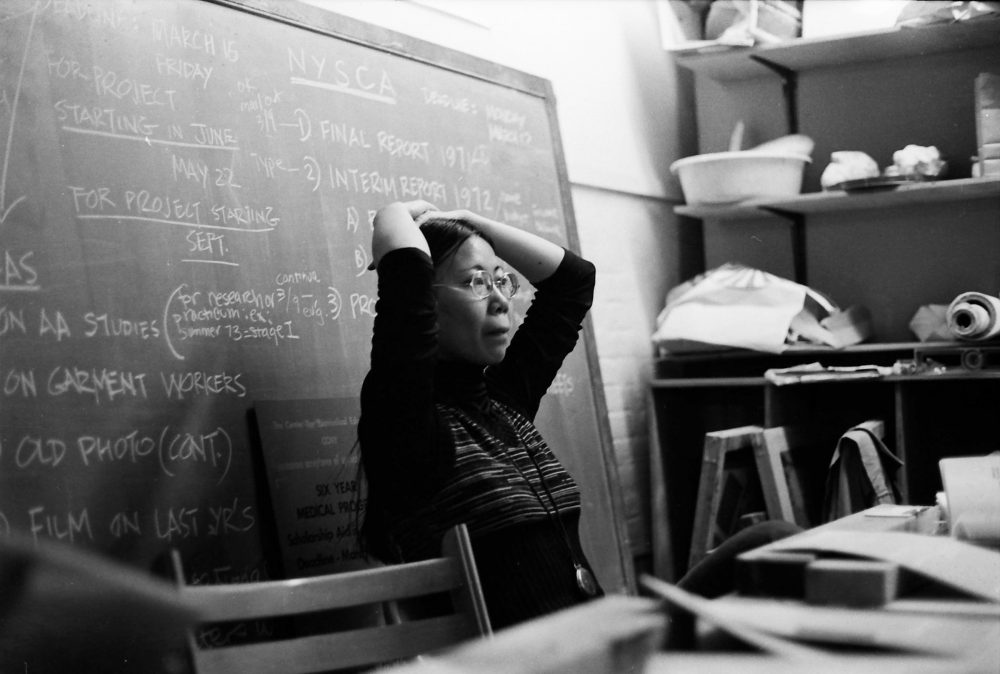 Black and white image of Fay Chiang sitting at a desk with her hands behind her head
