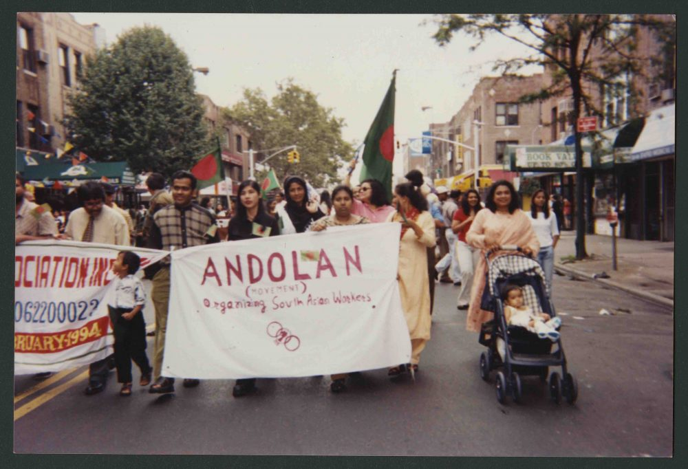 "Andolan members walk in a group behind a sign that reads ""Andolan, Organizing South Asian Workers"""