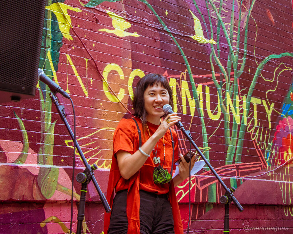 """Jess X. Snow stands in front of a microphone and their mural """"In The Future, Our Asian Community is Safe"""""""